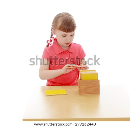 Keen little girl blonde short bangs and braids in which the braided ribbons in red shirt sitting at the table and examines Montessori material, the girl goes to Montessori kindergarten-Isolated on - stock photo