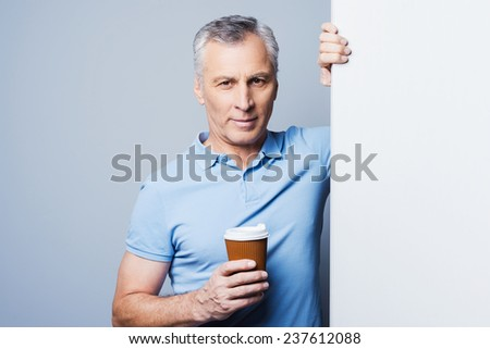 Keep calm and drink coffee. Handsome senior man holding cup of coffee and leaning at copy space while standing against grey background - stock photo