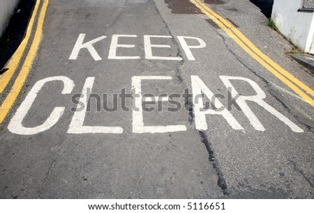Keep clear written in white paint on a road surface. - stock photo