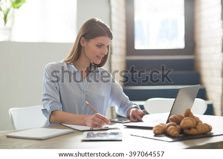 Keep everything on paper. Nice positive attractive woman sitting at the table and making notes while working on the laptop