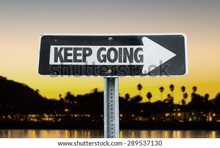 Keep Going direction sign with sunset background - stock photo