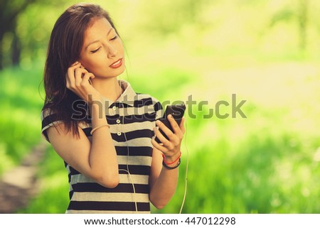 Keep in touch concept. Portrait of beautiful girl wearing striped t-shirt using smartphone in park. Sunny summer (autumn) weather. Close up. Copy-space. Outdoor shot