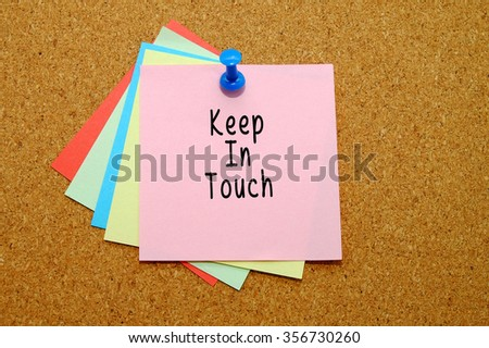 keep in touch written on color sticker notes over cork board background.