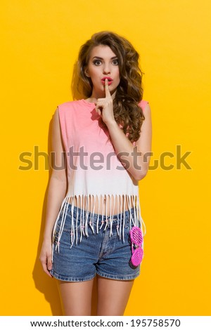 Keep it private! Beautiful young woman is holding index finger on a lips. Three quarter length studio shot on yellow background. - stock photo