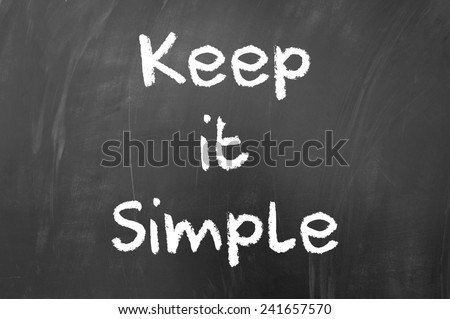 Keep it simple quote written with white chalk on blackboard