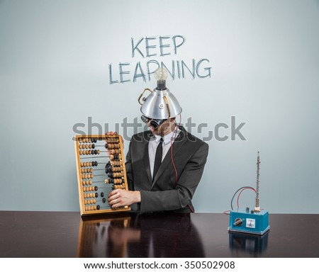 Keep learning concept with businessman and abacus - stock photo