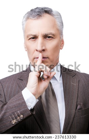 Keep my secret!  Serious mature man in formalwear holding finger on lips and looking at camera while standing against white background - stock photo
