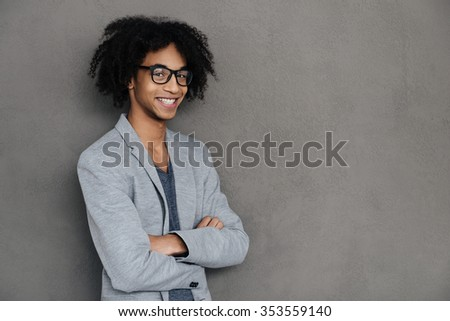 Keep on smiling. Cheerful young African man looking at camera with smile and keeping arms crossed while standing against grey background - stock photo