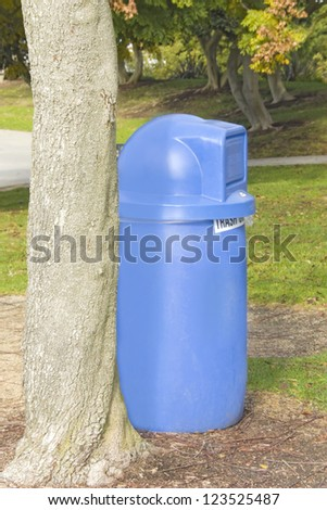 Keep our park clean. A blue plastic trash can is conveniently placed beside a tree in a grassy suburban park.