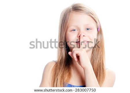 Keep silence! Pretty smiling little girl holding finger on mouth and looking at camera while standing isolated on white background - stock photo