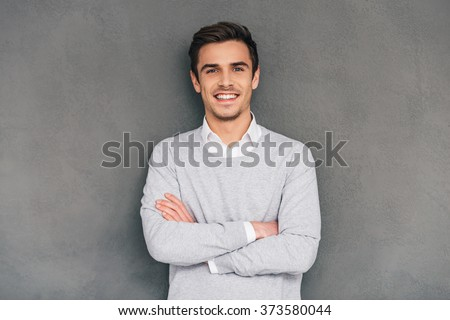Keep smiling. Confident young man keeping arms crossed and looking at camera with smile while standing against grey background - stock photo