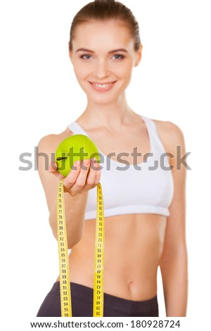 Keep your body in shape! Beautiful young woman in sports clothing holding apple and measuring tape outstretched and smiling while standing isolated on white - stock photo