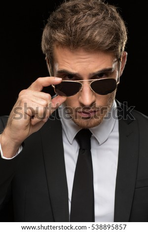 Keeping an eye on you. Vertical closeup of a handsome young man wearing classic suit peering over his sunglasses to the camera on black background