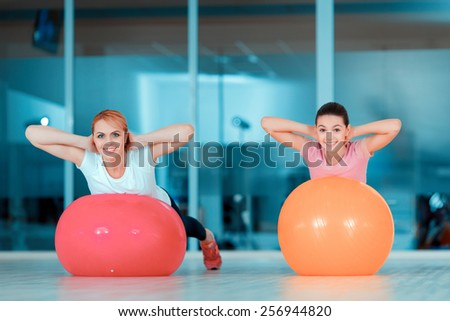 Keeping fit and feeling great. Beautiful teenage girl and her mother in sports clothing training on fitness balls against glass wall in sports club  - stock photo