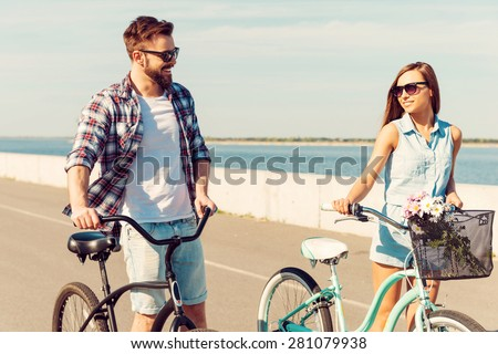 Keeping fit and having fun. Happy young couple rolling their bicycles and looking at each other with smile while walking outdoors - stock photo