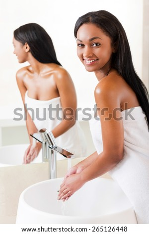Keeping her body clean and fresh. Beautiful young African woman washing hands in bathroom and looking over shoulder  - stock photo