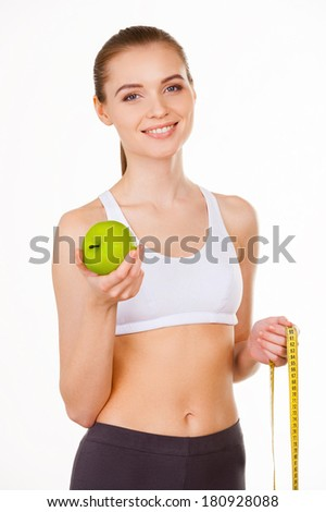 Keeping her body in shape. Beautiful young woman in sports clothing holding apple and measuring tape and smiling while standing isolated on white - stock photo