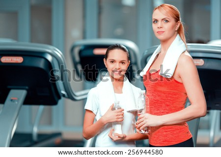 Keeping in shape. Attractive mature woman and her daughter in sports clothing holding bottle of water while standing in health club with a towel on their shoulders - stock photo