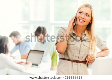 Keeping in touch with clients. Cheerful young woman talking on the mobile phone and smiling while her colleagues working in the background - stock photo