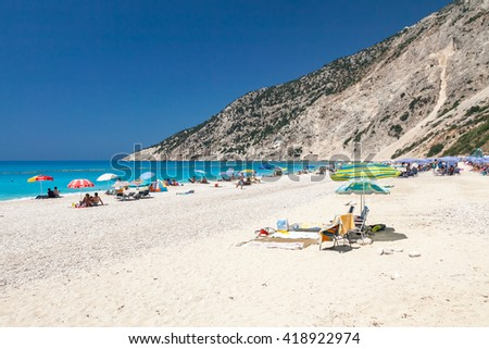 KEFALONIA, GREECE - JULY 23, 2009: Summer high season on Myrthos beach, Kefalonia island, Greece. Myrtos beach is famous due its snow white pebbles and sand. - stock photo