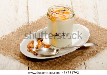 kefir in a glass with sweet honey, nuts and fruit and spoon on oval plate