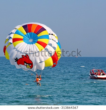 KEMER, TURKEY - AUGUST 12, 2015: Parasailing in a blue sky near sea beach. Parasailing is a popular recreational activity among tourists in Turkey.
