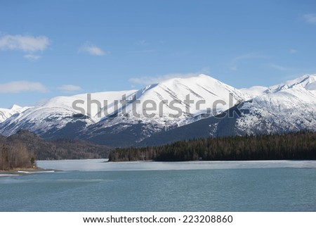 Kenai River running through the Kenai Peninsula below snow covered mountains - stock photo