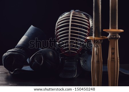 Kendo equipment over dark background: men, kote and shinai - stock photo