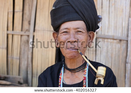 KENGTUNG, MYANMAR - JANUARY 20, 2016: A portrait of an Akhu hill tribe woman smoking her pipe in her village in Kengtung. The Akhu are an indigenous hill tribe living in Eastern Myanmar.