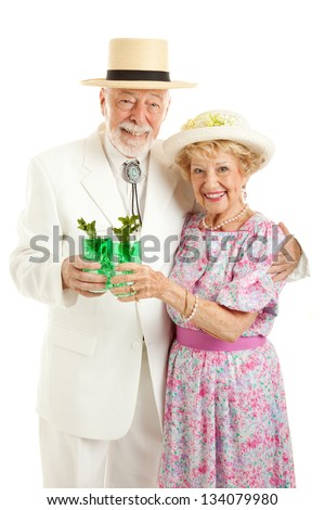 Kentucky Colonel and his wife dressed up and drinking mint juleps in celebration of Kentucky Derby Day.  Isolated on white. - stock photo