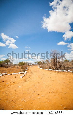 Kenya. Blue sky on this orange road in the middle of African Savana, Tsavo East National Park - stock photo