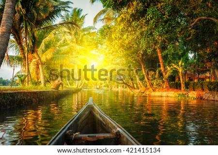 Kerala backwaters tourism travel in canoe on sunset. Kerala, India - stock photo