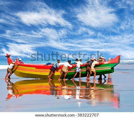 KERALA, INDIA - FEBRUARY 4, 2010: Indian fishermen carrying wooden boat at Indian ocean shore in Kerala state, South India