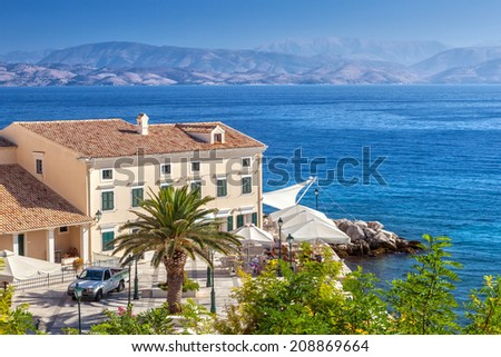 KERKYRA, CORFU, GREECE - SEPTEMPER 24 2013: Cafe at building standing on the embankment of Ionian sea with mountains in back.  - stock photo