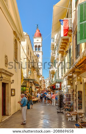 KERKYRA, CORFU, GREECE - SEPTEMPER 24 2013: Tourists walking and shopping on narrow streets with bell tower of Saint Spiridon church in background. - stock photo