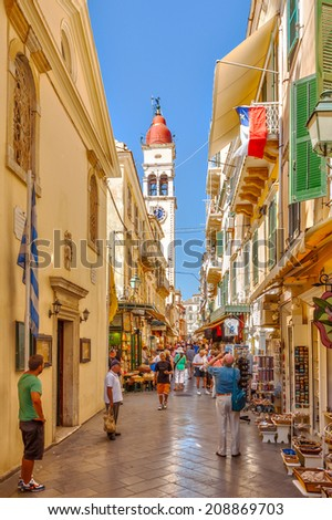 KERKYRA, CORFU, GREECE - SEPTEMPER 24 2013: Tourists walking and shopping on narrow streets with bell tower of Saint Spiridon church in background.