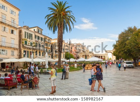KERKYRA, GREECE - SEPTEMBER 16: View to the Kapodistriou street with cafe tables and tourists shown on 16 September 2013 in Kerkyra, Greece.