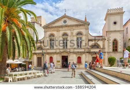 KERKYRA, GREECE - SEPTEMPER 19 2013: Tourists walking at the city center looking to the old churches and historical buildings. Also, some sitting and relaxing at cafe on Platia Dimarchiou.