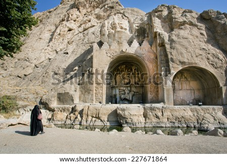 KERMANSHAH, IRAN - OCT 12: Lonely woman in muslim dress hijab standing near the monument Taq-e Bostan on October 12 2014. Taq-e Bostan is rock relief from 4 century, era of Sassanid Empire of Persia