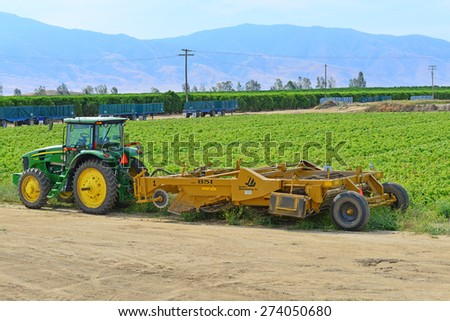 KERN COUNTY, CA - APR 29, 2015: Tractors, trailers and harvesting machines are converging on this San Joaquin Valley farm field in preparation for the potato harvest. - stock photo