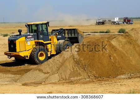 KERN COUNTY, CA - AUG 20, 2015: A front end loader scoops up excess dirt on a construction project as a bottom dump truck approaches to receive the material.