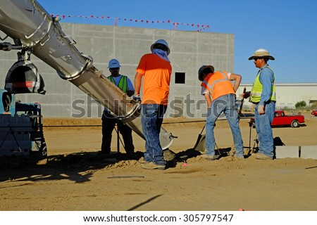 KERN COUNTY, CA - AUGUST 11, 2015 : A transit mix truck delivers concrete down a chute while workers place the wet material in a ditch to serve as a footing for a block wall.