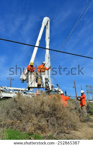 KERN COUNTY, CA - FEBRUARY 14, 2015: The crew of a contractor to PG&E uses a hydro crane with a basket to set a new wood pole and stabilize it with guy wires in difficult terrain.