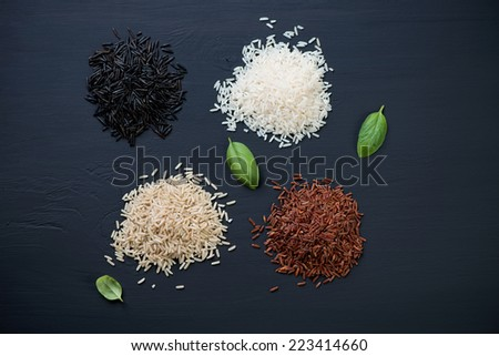 Kernels of red, brown, white and black rice, view from above - stock photo