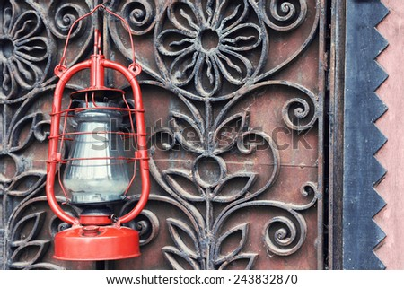 Kerosene lamp on wrought iron gates background - stock photo