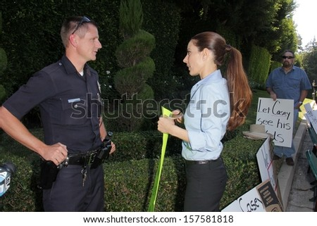 Kerri Kasem talks to the police officer at a protest involving Casey Kasem's children, brother and friends who want to see him but have been denied any contact, Holmby Hills, CA 10-01-13 - stock photo