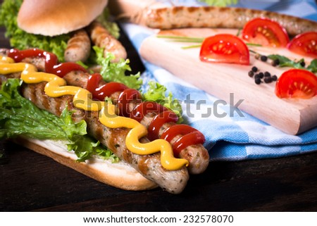 Ketchup and mustard on the grilled sausages,selective focus  - stock photo