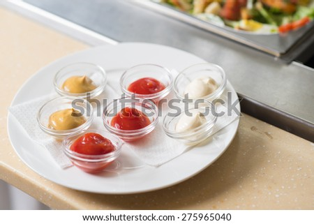 ketchup and mustard on the plate on a table in a restaurant - stock photo