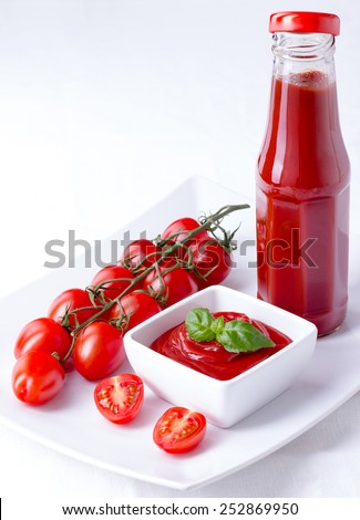 ketchup, catsup in a glass bottle and a white bowl with cherry panicles tomatoes isolated on white background, vertical closeup, copy space - stock photo