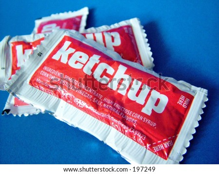 Ketchup packets on blue background, close up